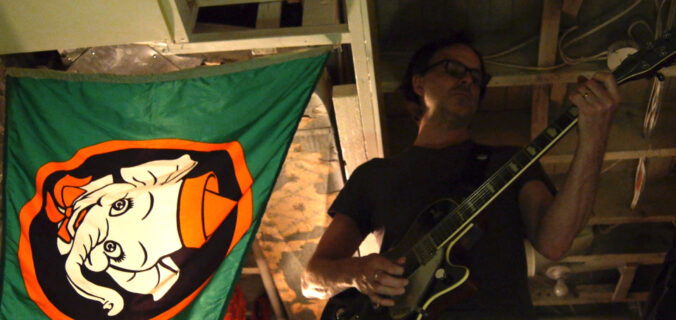 bgm playing a Gretsch Duojet under a flag of Elmer the Safety Elephant